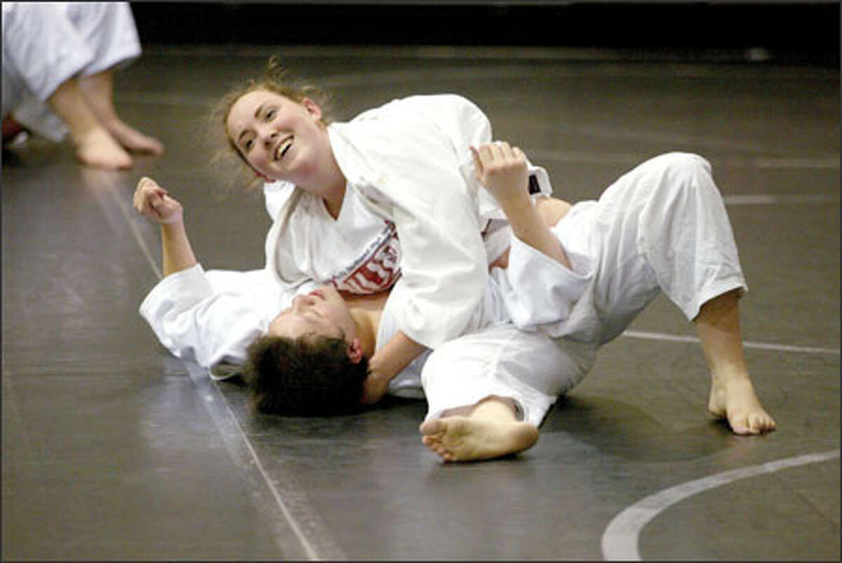 Kentwood High senior Sarah Collins is quite pleased after pinning junior Alan Lo in judo practice. Kent will hold a reunion in April of its many judo participants.