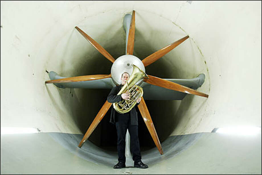 "Seattle Symphony principal tuba player Christopher Olka stands in the F.K. Kirsten Wind Tunnel where the late Boeing engineer -- and tuba player -- James Crowder once worked. Samuel Jones, whose concerto was commissioned in Crowder's memory, wants to replicate the tunnel's ""huge, compelling sound."" Photo: Mike Urban, Seattle Post-Intelligencer / Seattle Post-Intelligencer"