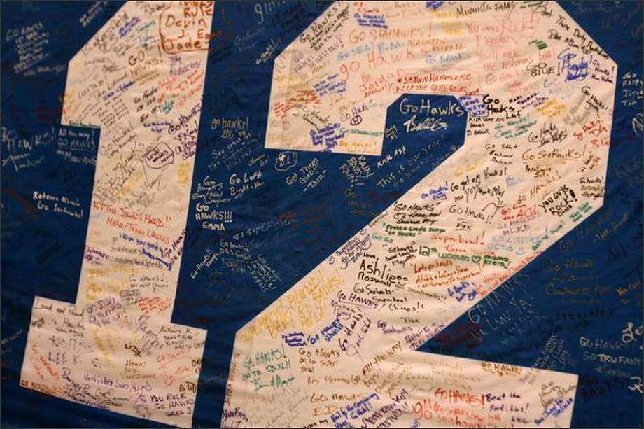 Dozens of fans signed a 12th Man flag at a Seahawks pep rally at Qwest Field on Friday. Photo: Mike Urban, Seattle Post-Intelligencer / Seattle Post-Intelligencer