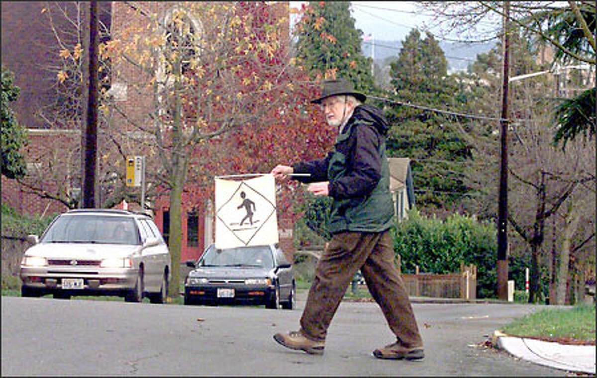 Lester Goldstein, a member of a pedestrian advocacy group called Feet First, breaks out his little flag to stop traffic as he crosses an unmarked area of 40th Avenue North.