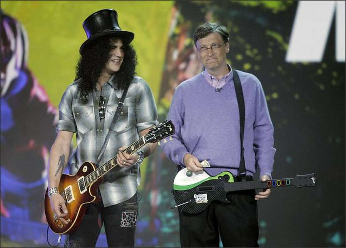 Microsoft chairman Bill Gates, right, introduces guitarist Slash as his ringer in a friendly