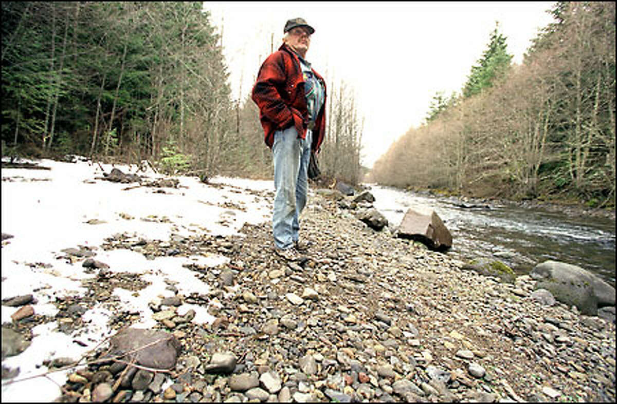 Jerry Trussell stands beside the Greenwater River, where a right-to-log fight is under way.
