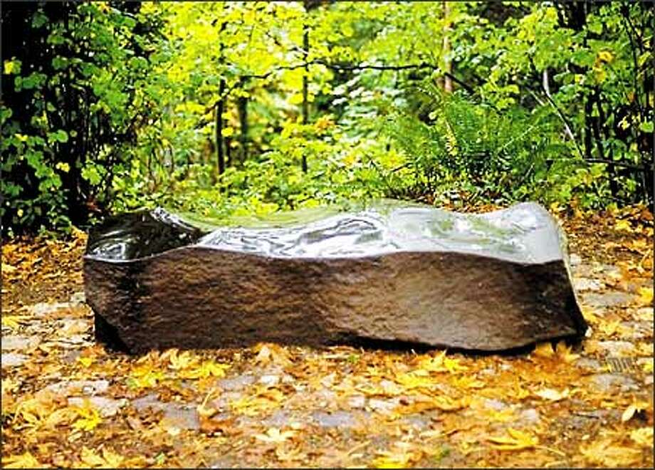 Bobbie Baker commissioned this basalt bench in Interlaken Park as a memorial to her husband, Rob Reed, who died in a plane crash in 1993. Reed, a producer for KCTS/9, was on assignment near Longview. Photo: Paul Joseph Brown, Seattle Post-Intelligencer / Seattle Post-Intelligencer