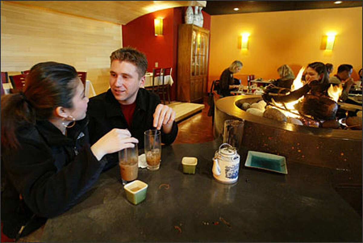 Cindy Pham and Ian McKamey find a quiet spot by the fire pit for their first visit to Tamarind Tree Vietnamese restaurant in the Little Saigon area of Seattle's International District.
