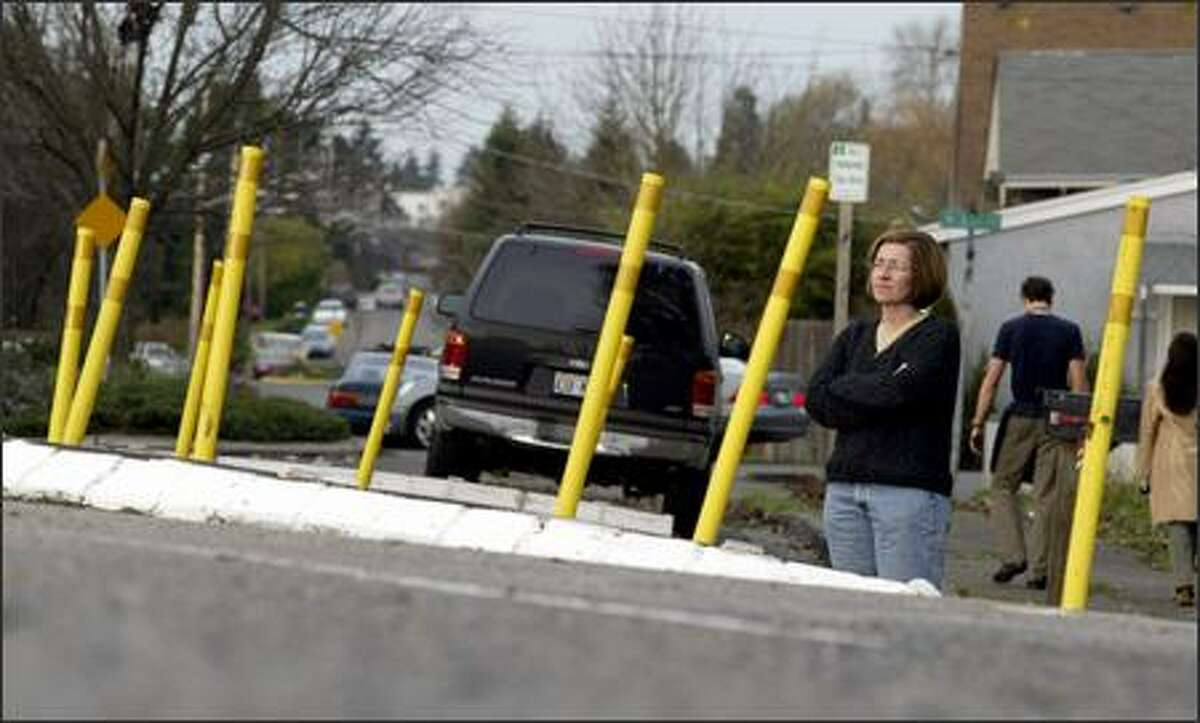 Kate Martin, a Greenwood neighborhood activist, stands on the side of Palatine Avenue North to show how high the street buckles in the middle, the result of changing groundwater conditions.