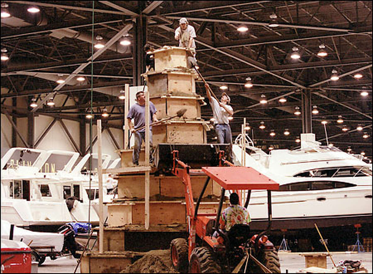 Ted Siebert (left), owner of The Sand Sculpture Company, shovels sand loam to the top of a sculpture that will be carved into a 25-foot lighthouse and will be on display during the Seattle Boat Show at the Stadium Exhibition Center Jan. 11-20. Siebert will be finishing the lighthouse during the boat show.