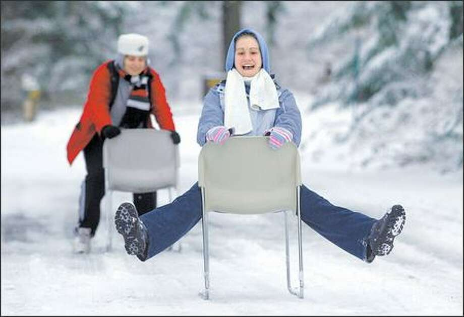 With classes cancelled because of the snow, juniors Shelby Jones, foreground, of Everett and Mays Salamah of Puyallup use chairs from their dorm yesterday to slide down a street on the Western Washington University campus in Bellingham, which received 3 to 4 inches of snow. Photo: Dan DeLong, Seattle Post-Intelligencer / Seattle Post-Intelligencer