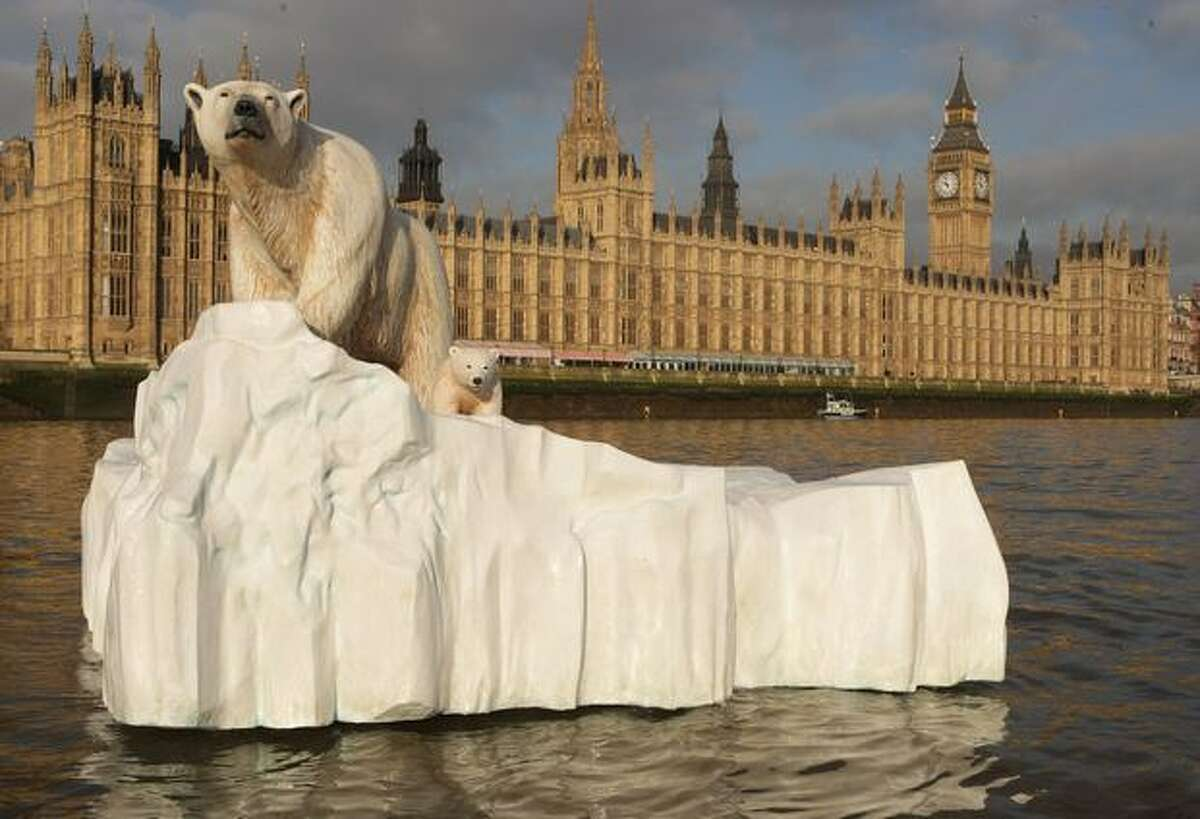 A 16-foot-high sculpture of a polar bear and cub, afloat on a small iceberg, passes in front of the Houses of Parliament on the River Thames in London in this January 2009 file photo. The sculpture was launched to provide a warning to members of parliament of the dangers of climate change and to launch a new natural history television channel.