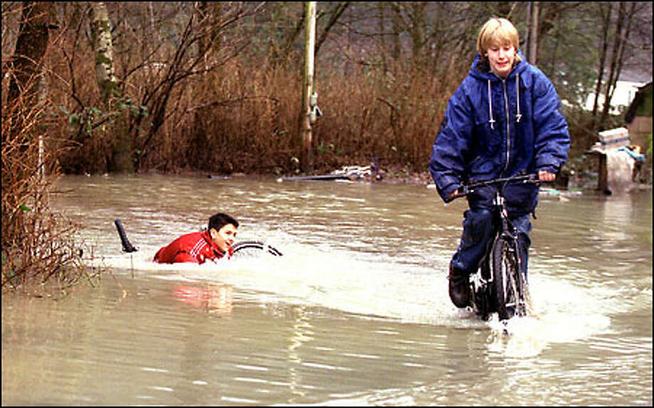 Brandon Irving, left, and Derik Shooster horse around in the water at a flooded trailer park on the Skagit River at Hamilton. They were on the way home from school when they decided to cruise a patch of water. Brandon hit a hole and got drenched. Rivers were on the rise in Western Washington yesterday, and some houses were flooded. Photo: Gilbert W. Arias, Seattle Post-Intelligencer / Seattle Post-Intelligencer
