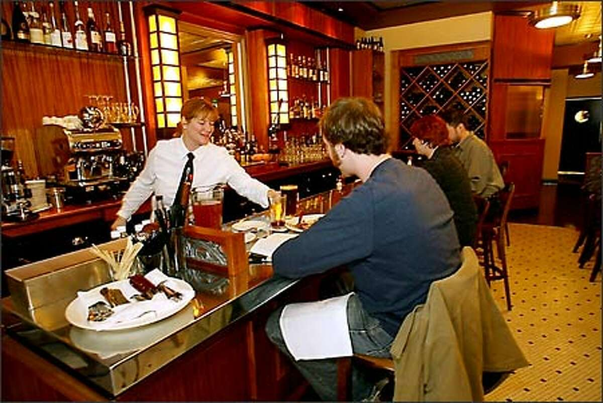 Gretchen Kenney, left, bar manager, serves a beer to Adam Levitt, center, at Bandol Restaurant while Monica Rasmussen and Alan Scott, far right, enjoy the moment.