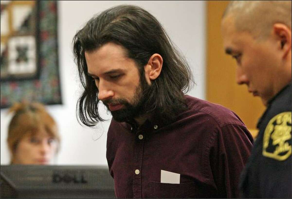 Joseph McEnroe is escorted from the courtroom after a hearing at the King County Courthouse in Seattle.