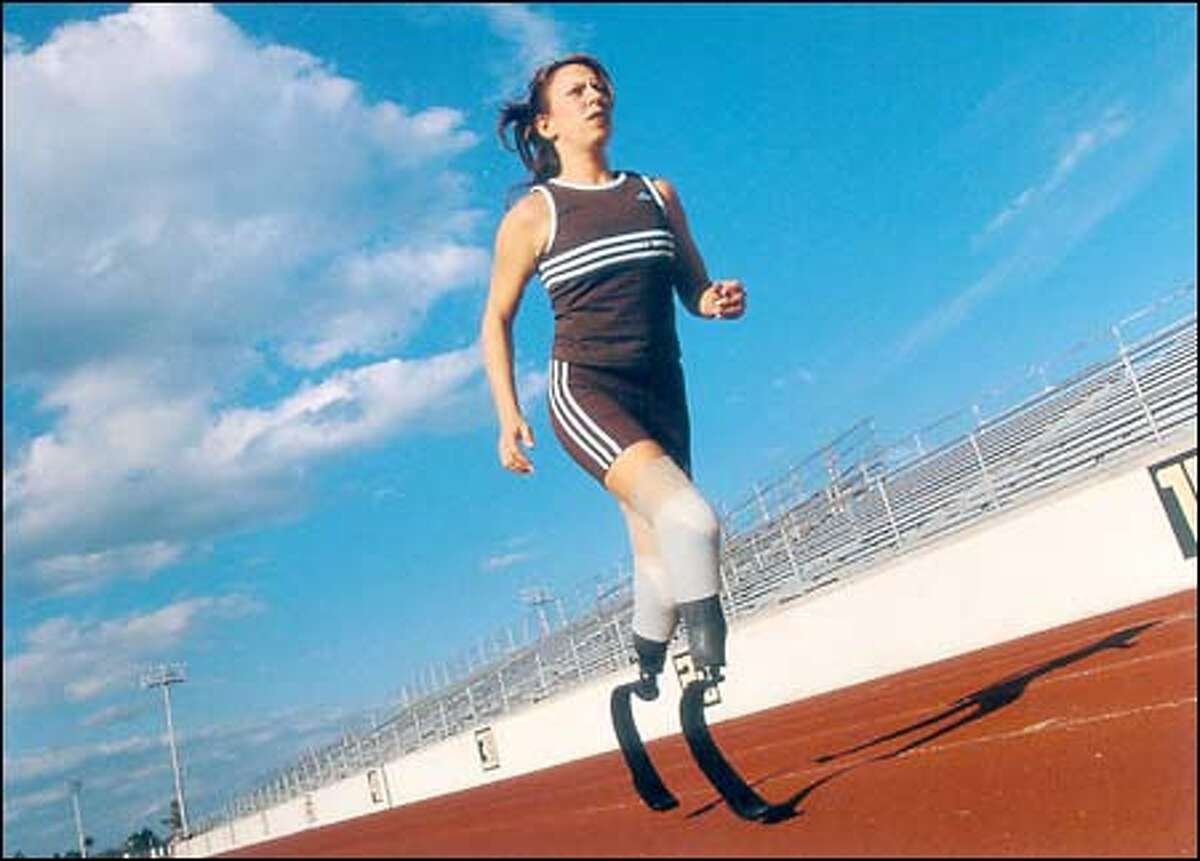 """The cover of Jami Goldman's book captures the determined runner rounding a track on her """"cheetah legs,"""" high-tech, carbon-fiber prostheses. (Photo by John Hall)"""