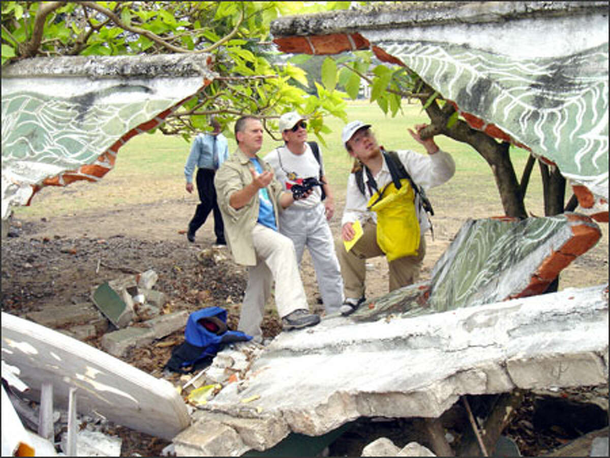 Tsunami researchers James Goff, Robert Morton and Bretwood Higman examine a wall damaged by the tsunamis Dec. 26 in Colombo, Sri Lanka.