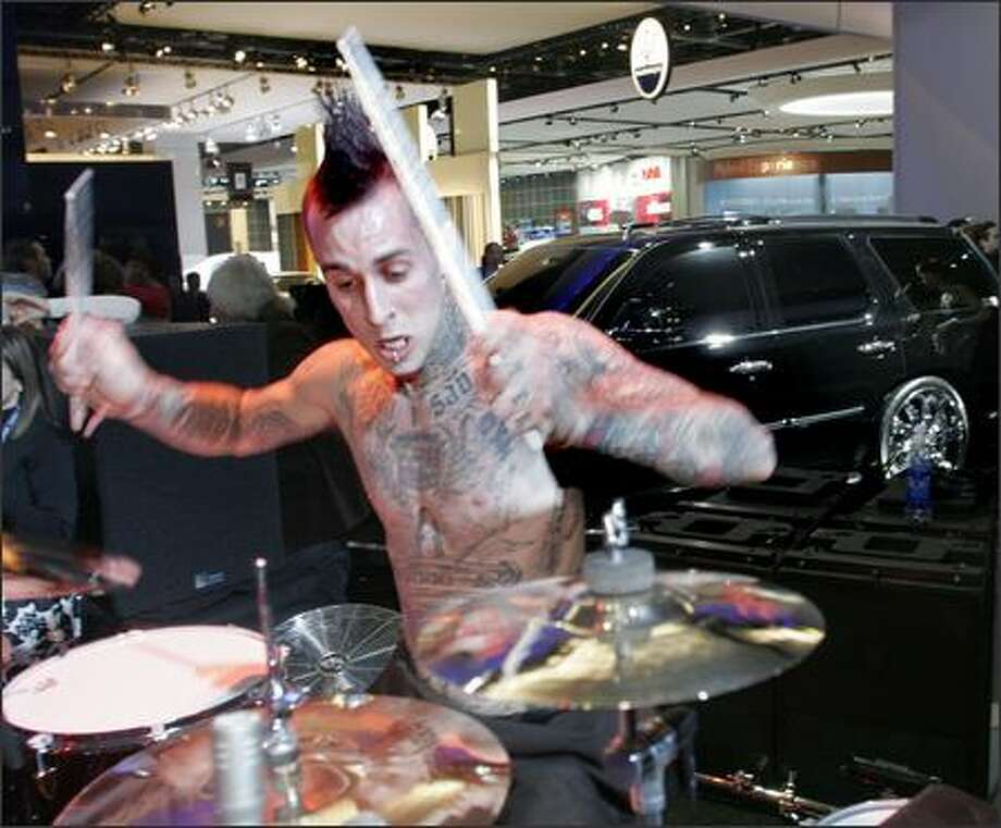Does this rock action truly make you want to run out and buy a Cadillac Escalade? Blink182 drummer Travis Barker pounds away during a Cadillac reception at the auto show in the Motor City. Perhaps the 2007 Escalade comes in a special Mr. Barker Edition featuring plush leather seats with replica Travis tattoos... Photo: Associated Press / Associated Press