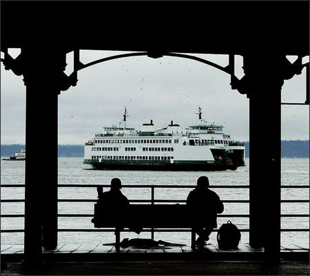 Two men sit Monday at the dilapidated Washington Street Public Boat Landing at the waterfront as a ferry departs for Bremerton.