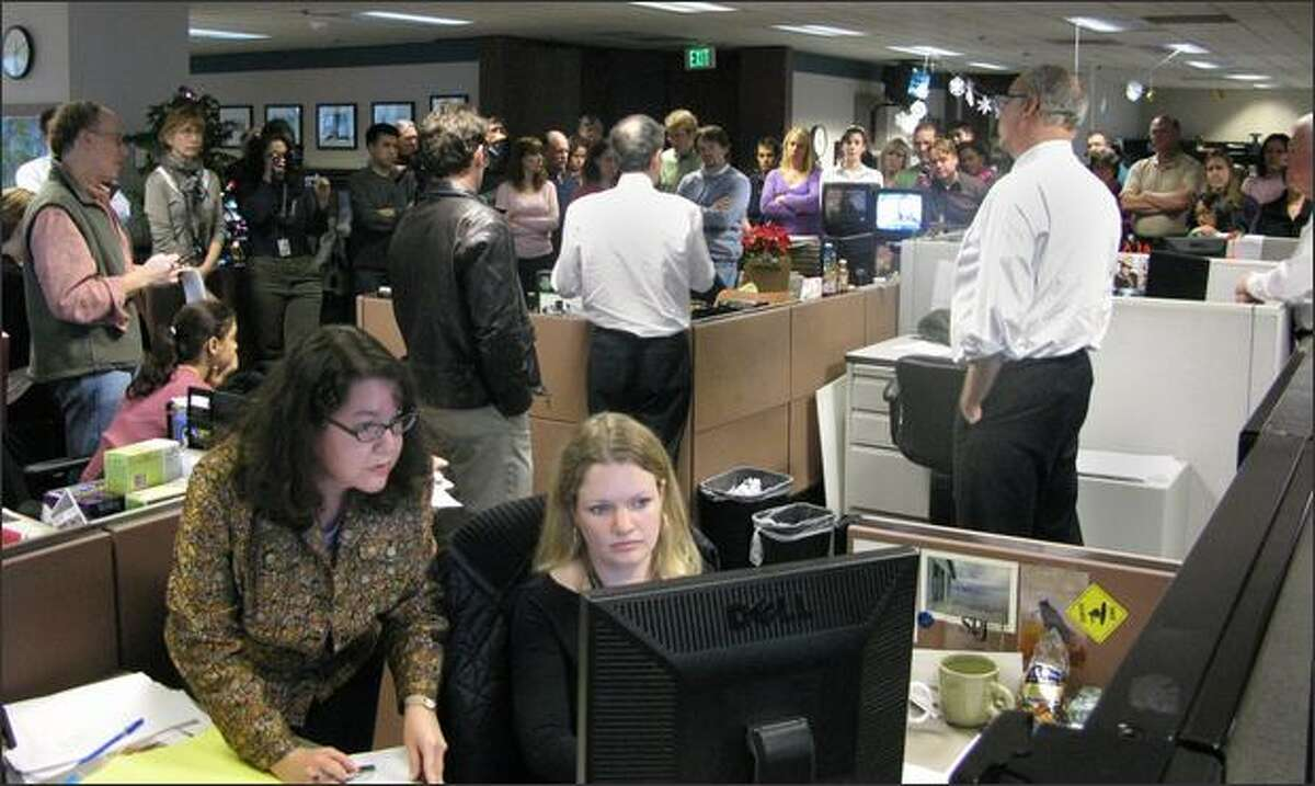 P-I business editor Margaret Santjer, left, works with senior online producer Sarah Rupp as they post a story about the P-I's being put up for sale. In the background, Steven Swartz, president of The Hearst Corp.'s newspaper division, addresses the staff. At right is managing editor David McCumber.