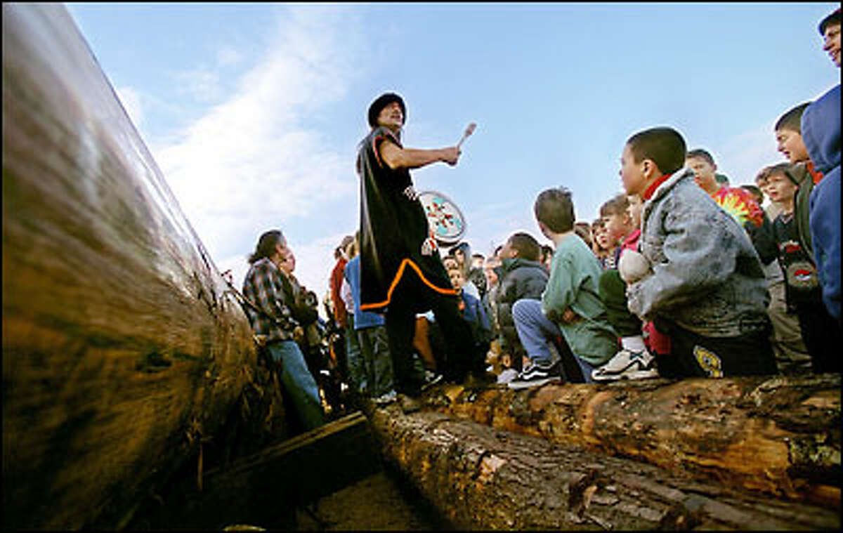 Haida carver Robert Peele leads children of Seattle's Alternative School No. 1 in a blessing of a 41-foot log cut from a centuries-old cedar in British Columbia's Queen Charlotte Islands. The log will be shaped into an eight-person canoe.