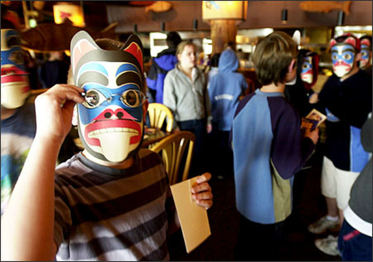 Pupils from Hazelwood Elementary School in Newcastle don Native American masks that were handed out yesterday at Ivar's Restaurant in Seattle as part of the