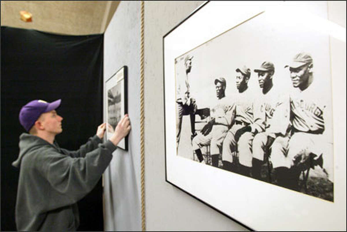 Paul Byrne, a 2002 graduate of Seattle's Chief Sealth High School, yesterday hangs a photo that is part of the Negro Leagues Baseball Museum's traveling exhibit. The Negro leagues were the only forum for black players until Jackie Robinson broke the color barrier in baseball in 1947.
