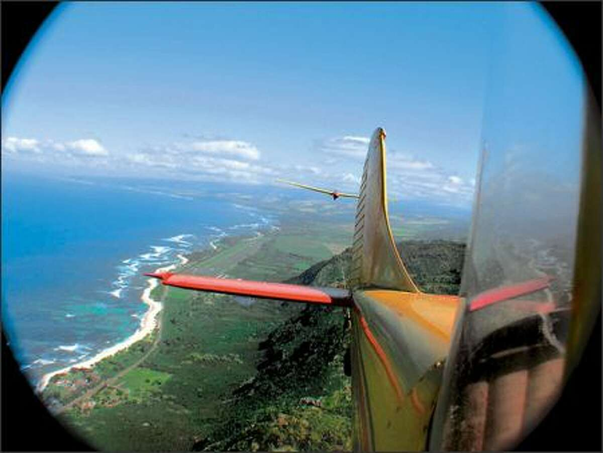 A tow plane pulls a glider aloft over the Oahu coast. After release, the glider generally will cover a radius of five to six miles during its 20-minute flight. The aircraft can carry up to two passengers.