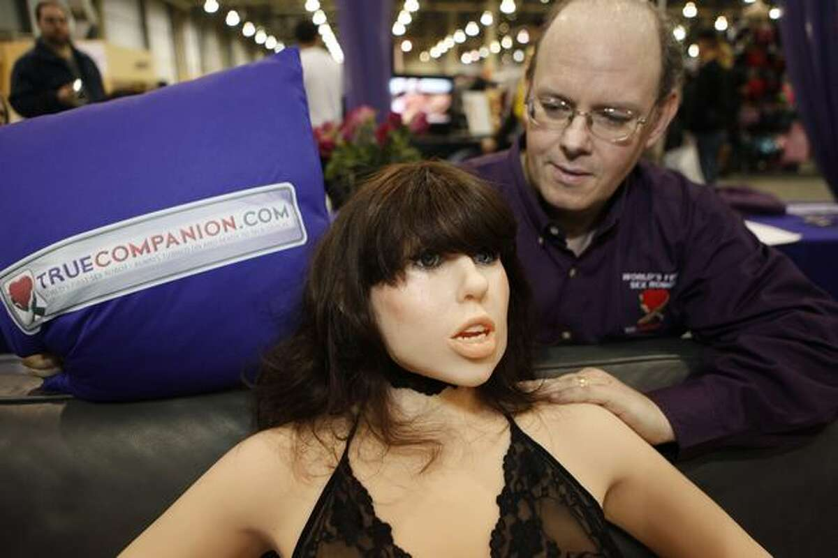 Douglas Hines, founder of True Companion, poses with a life-size rubber doll named Roxxxy during the Adult Entertainment Expo in Las Vegas on Saturday. (AP Photo/Paul Sakuma)