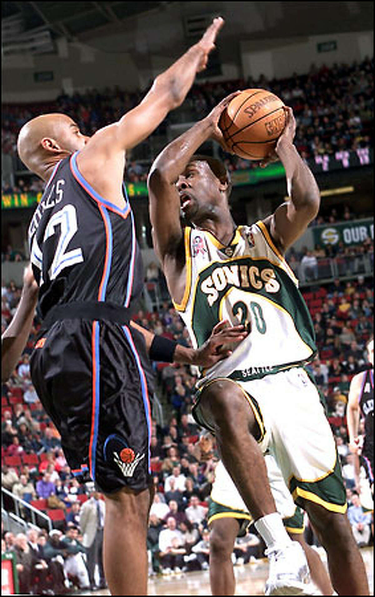 Gary Payton drives on Bimbo Coles. Payton had 24 points as the Sonics defeated Cleveland for the 13th consecutive time.
