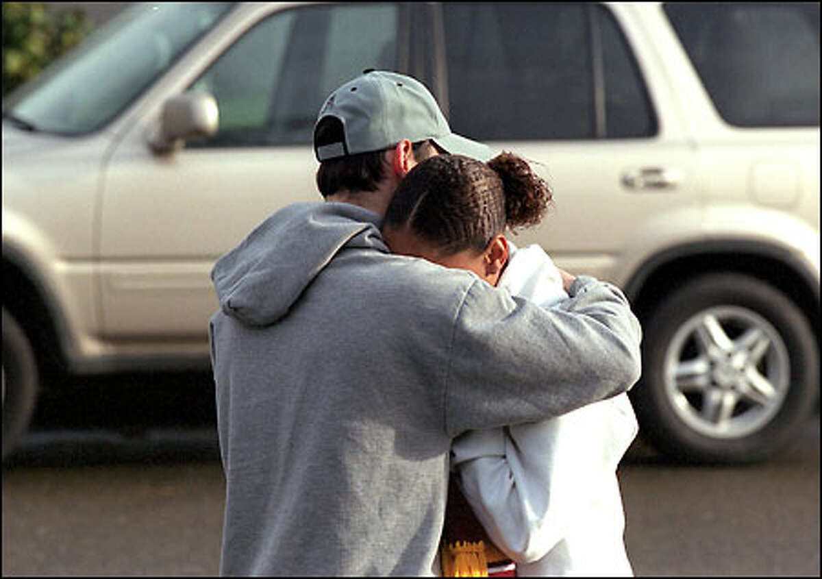 Russell Whitaker II's best friend, Anthony Vaughn, and girlfriend, Jeanette Geiger, embrace at the Whitaker home in South Tacoma after Whitaker's death.