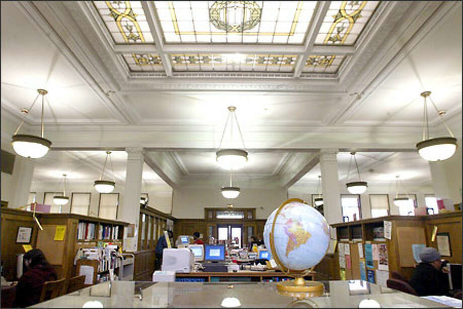 The interior of the Douglass-Truth Library in the Central Area looks spacious with its high ceilings and abundant lighting aided by the massive stained-glass skylight. Symmetrical reading rooms frame the east and west sides of the main entry. A third reading room on the north side is crammed with computers and book stacks. Photo: Joshua Trujillo, Seattlepi.com / seattlepi.com