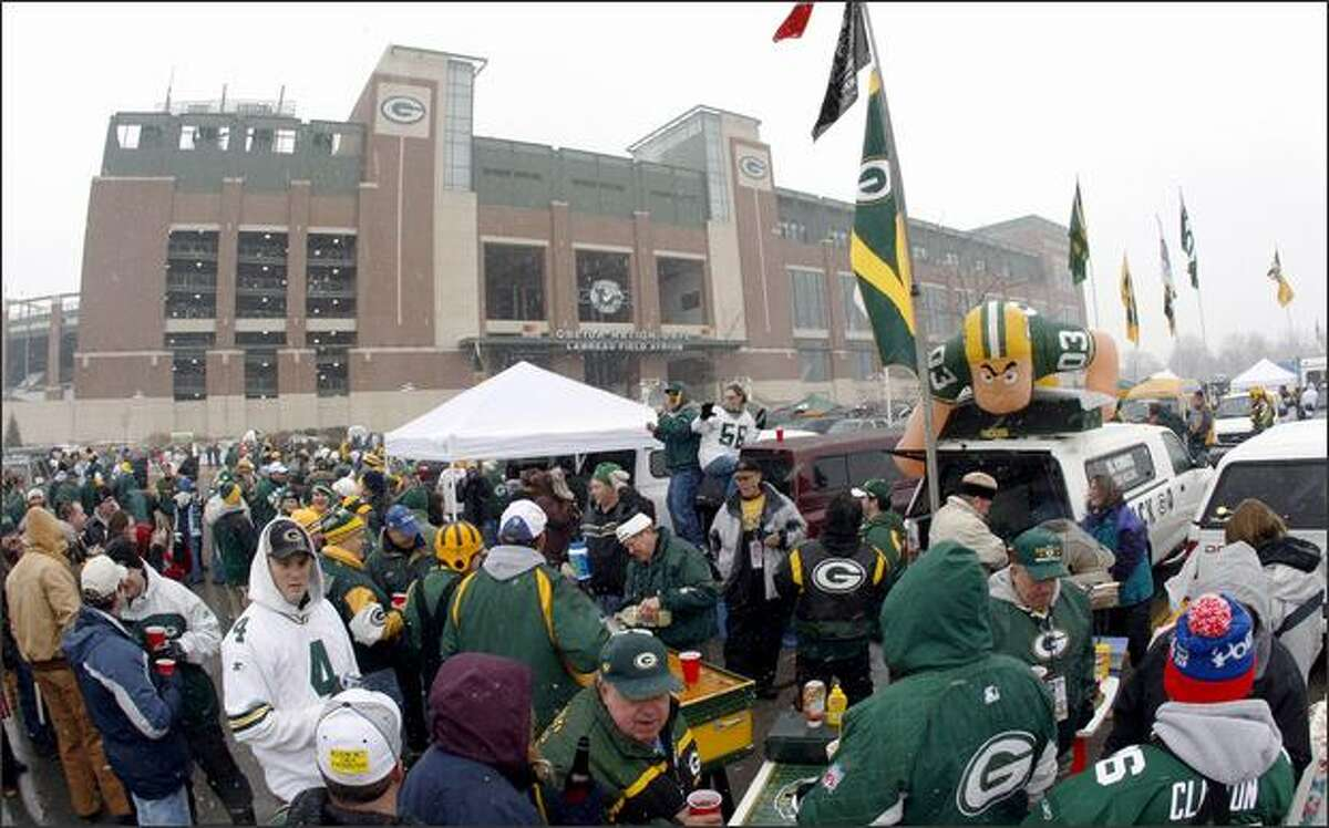 Fans tailgate outside Lambeau Field before an NFL football playoff game between the Green Bay Packers and the Seattle Seahawks on Saturday in Green Bay, Wis. (AP Photo/Mike Roemer)