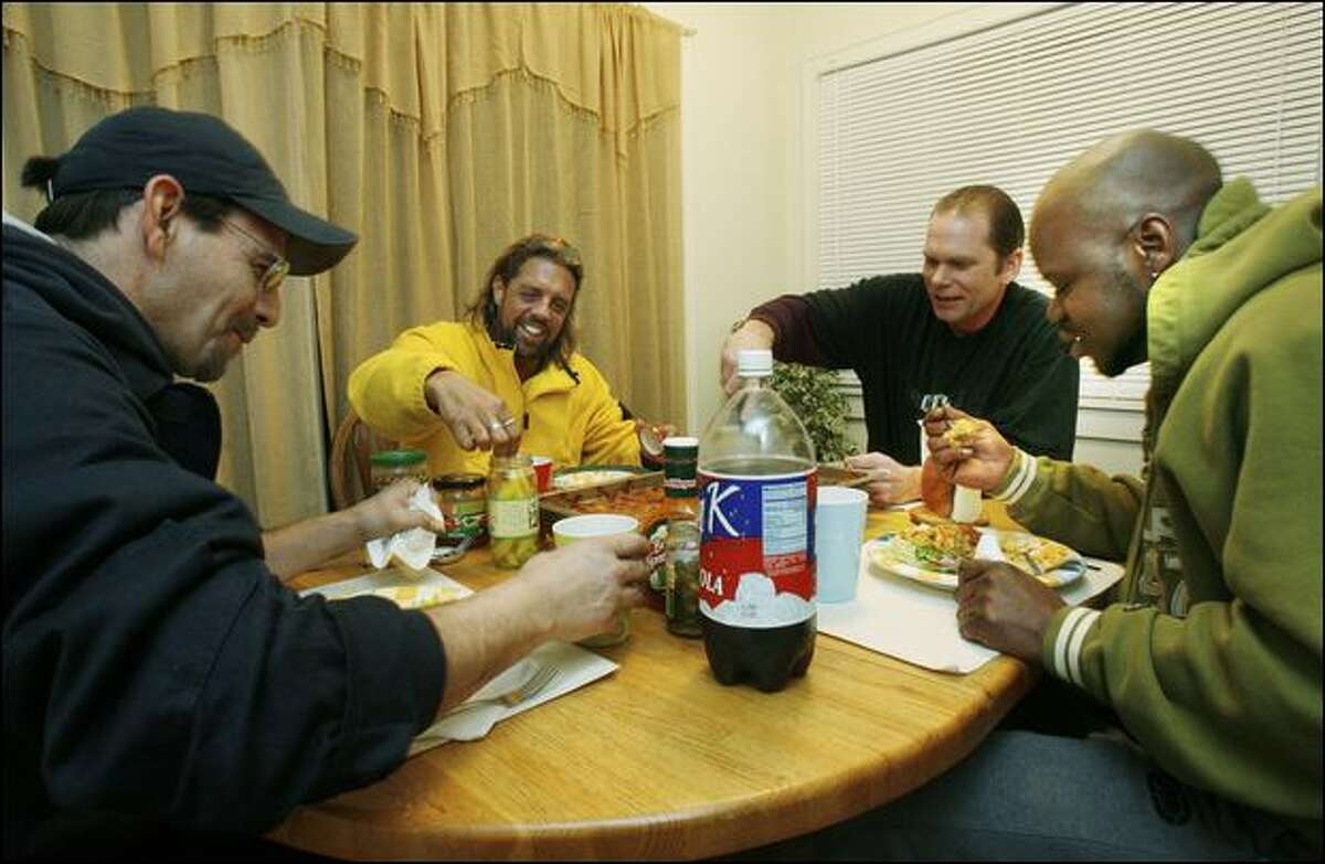 From left, Steve Rodriguez, Michael Campbell, Charles Capizano and Kelly Somerville, all formerly homeless, eat enchiladas Capizano made in the house they rented after CityTeam closed its shelter in December. Each man has been clean and sober for less than a year and all rely on each other to continue that success.