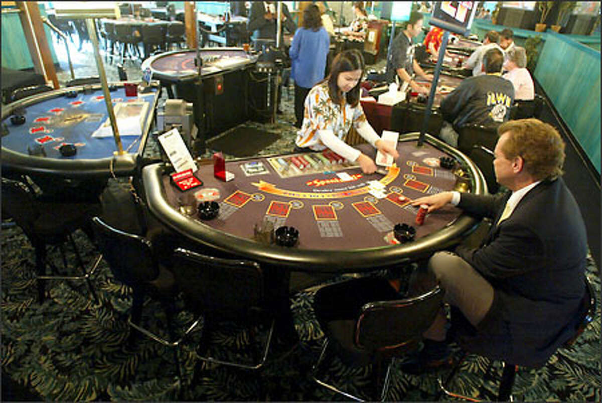 Betty Phan deals cards at Tukwila's Silver Dollar Casino. The minicasino can have 15 card tables, but can't run games such as craps or video slot machines.