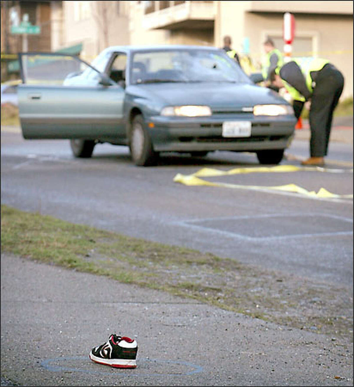 The shoe of a Ballard High student who was hit by a car yesterday remains in the street as Seattle police investigators look over the vehicle.