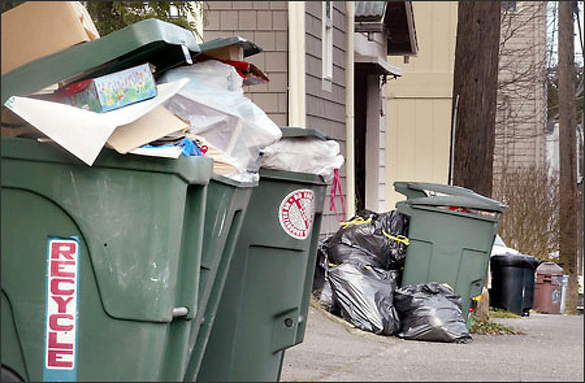 Overflowing bins of garbage and recyclables line an alley on Queen Anne yesterday. With any luck, it will be picked up today.
