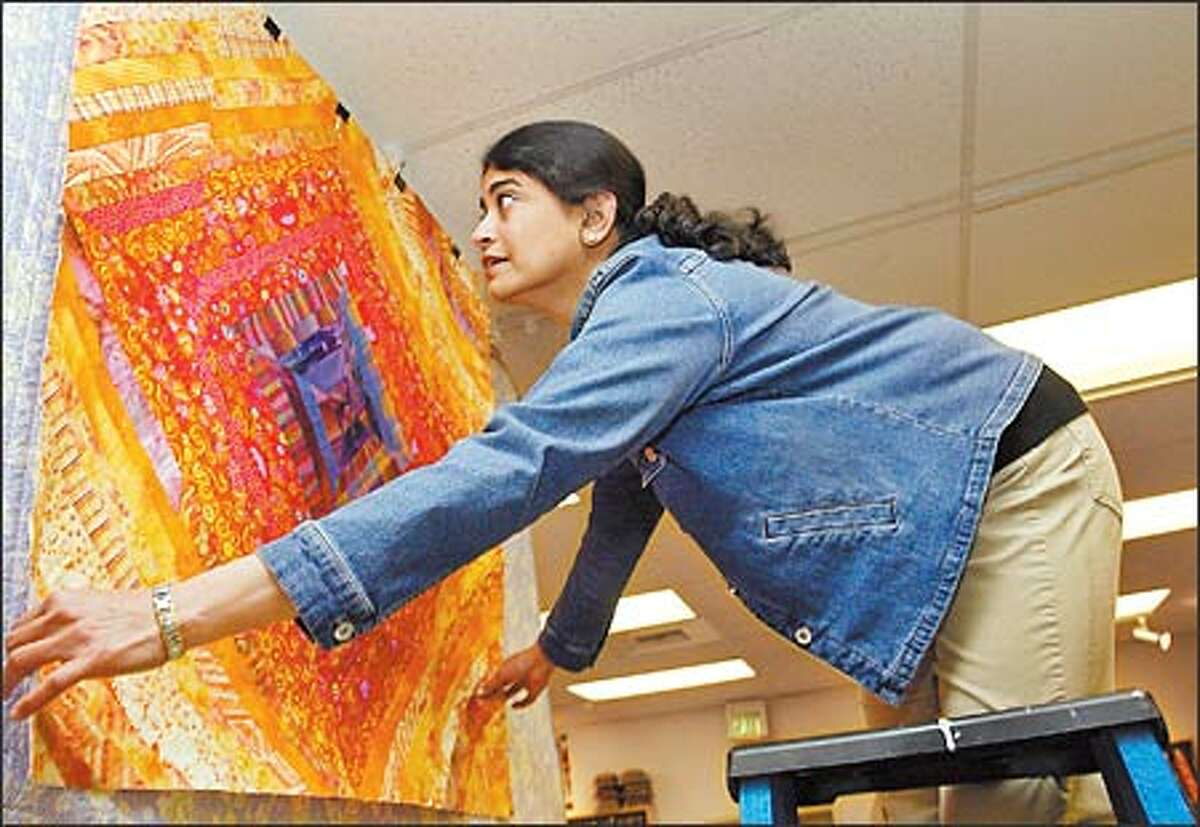 Sujata Shah, a teacher at QuiltWorks Northwest, hangs a Kaffe Fassett-inspired quilt that she made.