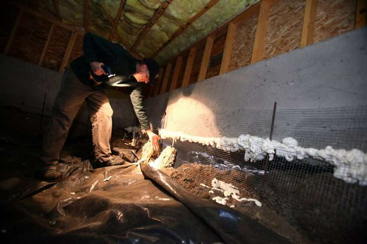 Alan Smith looks at the foundation in the crawl space of his Greenwood home on Tuesday. His home and part of the neighborhood were built on top of a peat bog that is slowly draining and sinking. The sinking earth has left the foundation of his home above ground, resting on piles.