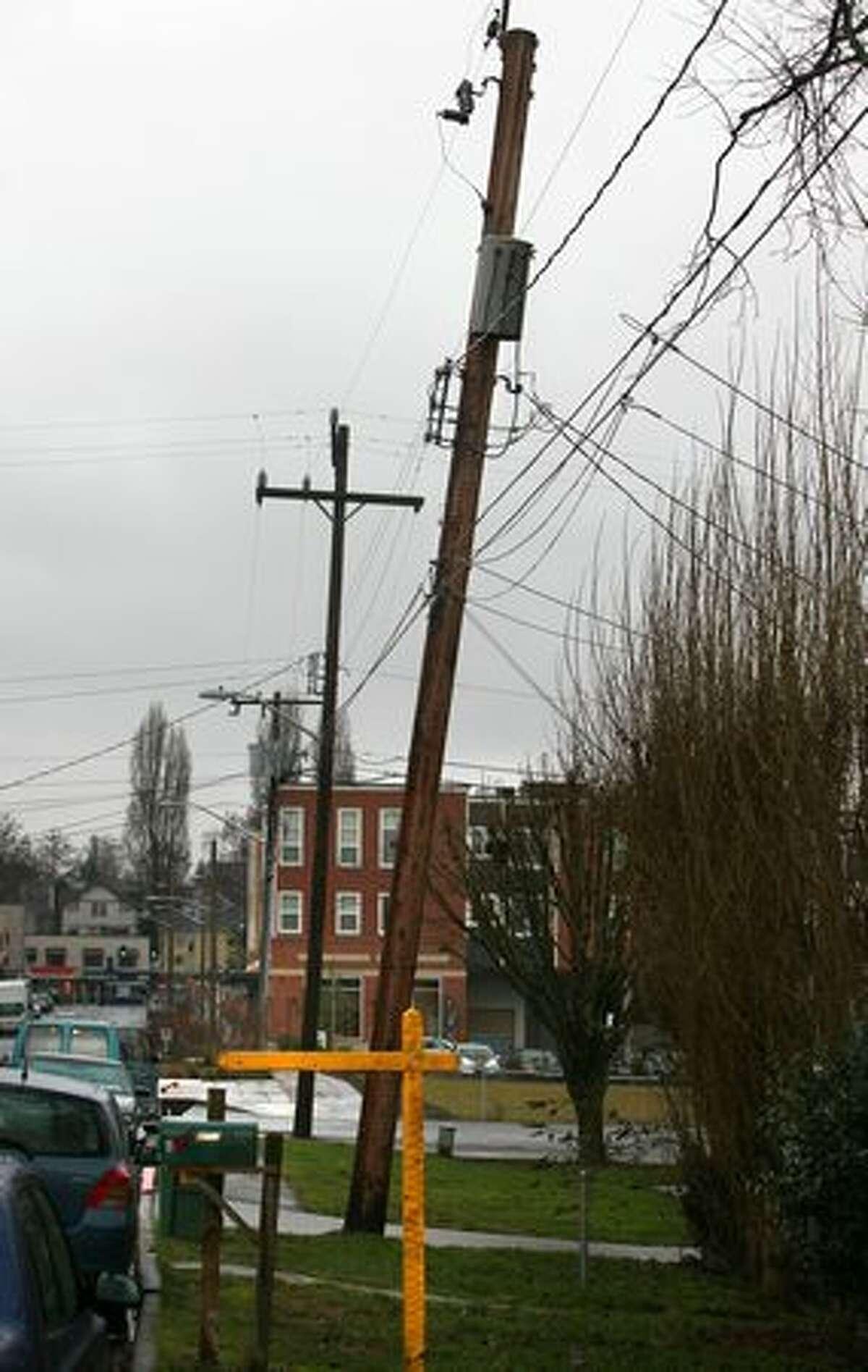 A telephone pole slowly sinks into the ground on Palatine Avenue North.