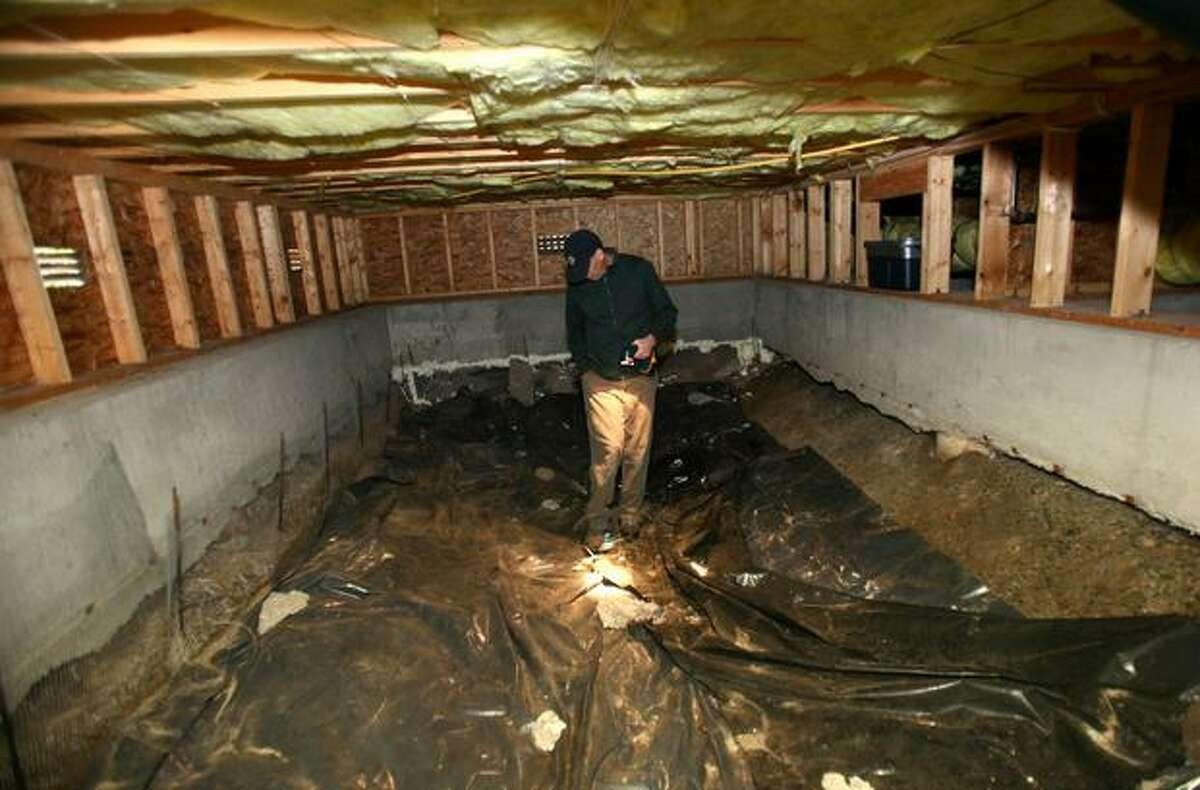 Alan Smith looks at the foundation in the crawl space of his Greenwood home.