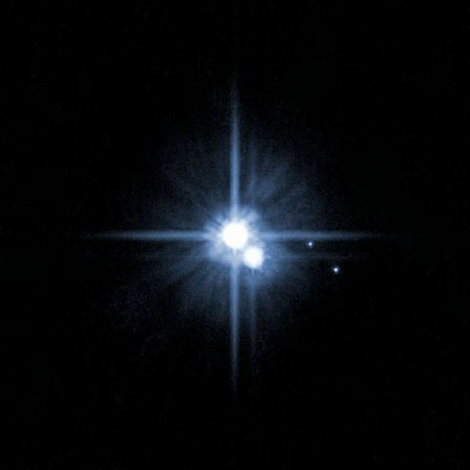 This undated image taken by the Hubble telescope shows Pluto and its moons: Charon, Nix, and Hydra. The International Astronomical Union announced on Aug. 24, 2006 that it no longer considers Pluto a planet, a status it has held since its discovery in 1930. The announcement reduces the solar system from nine planets to eight. Photo: Getty Images / Getty Images