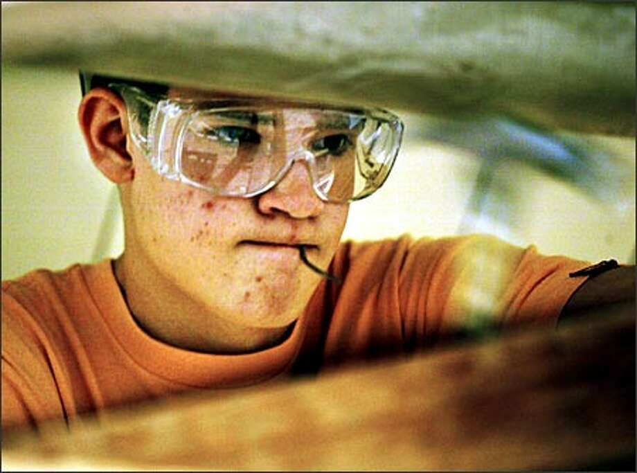 "Dan Rook, a Bothell High senior, is learning more than carpentry in his construction academy class. ""It teaches you how to be an adult and act like one,"" fellow senior Will Jones says. Photo: Renee C. Byer, Seattle Post-Intelligencer / Seattle Post-Intelligencer"