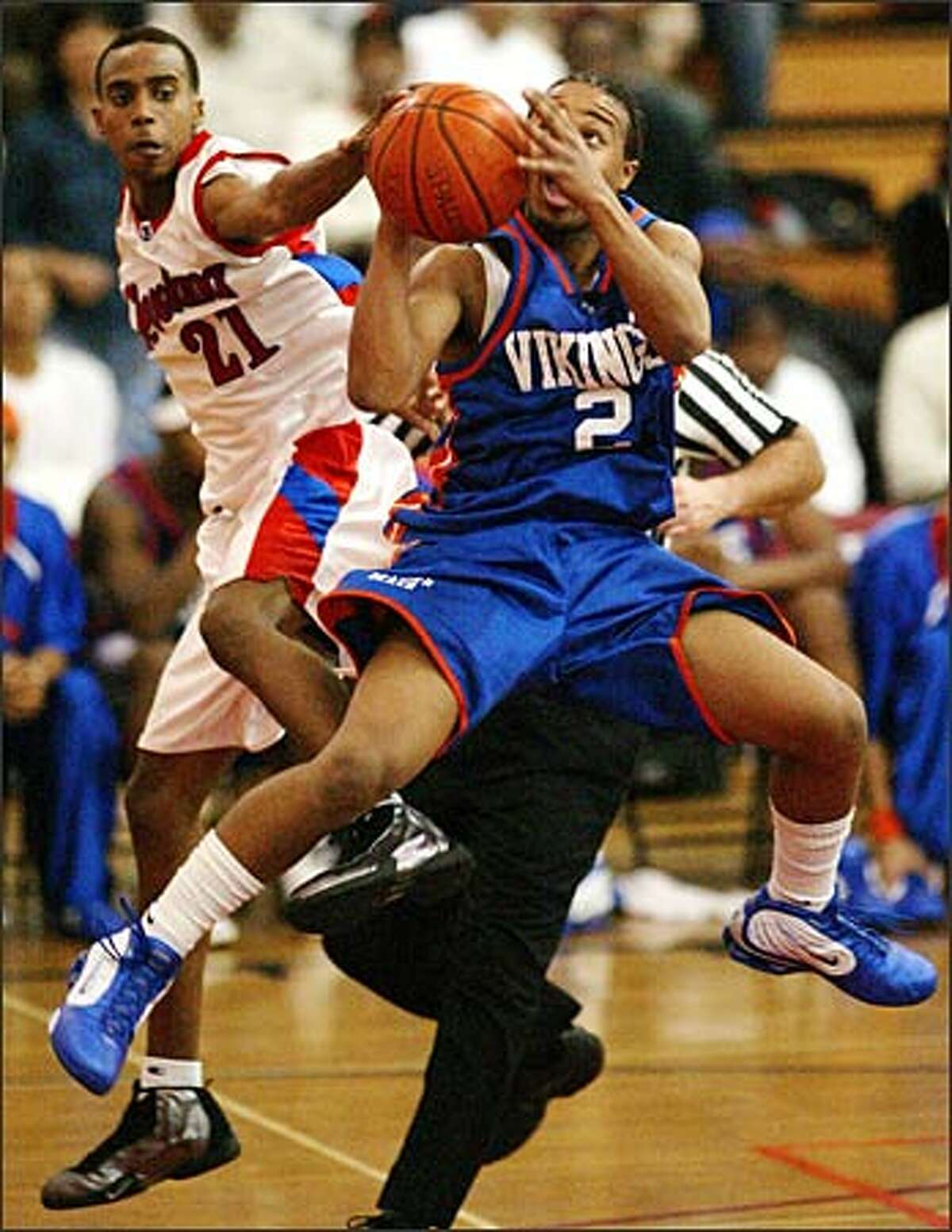 Cleveland's Antonio Sims blocks a shot by Rainier Beach's Dwayne Wright during Friday's game. Cleveland shocked the top-ranked Vikings 65-60.