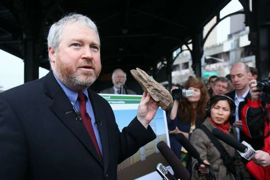 Seattle Mayor Mike McGinn holds up a piece of the seawall as he announces a city-funded rebuild of the Seattle seawall as a public safety concern on Thursday along Alaskan Way South. The mayor said citizens know the consequences of earthquakes and hopes voters will support a measure to fund the project. Photo: Joshua Trujillo, Seattlepi.com / seattlepi.com