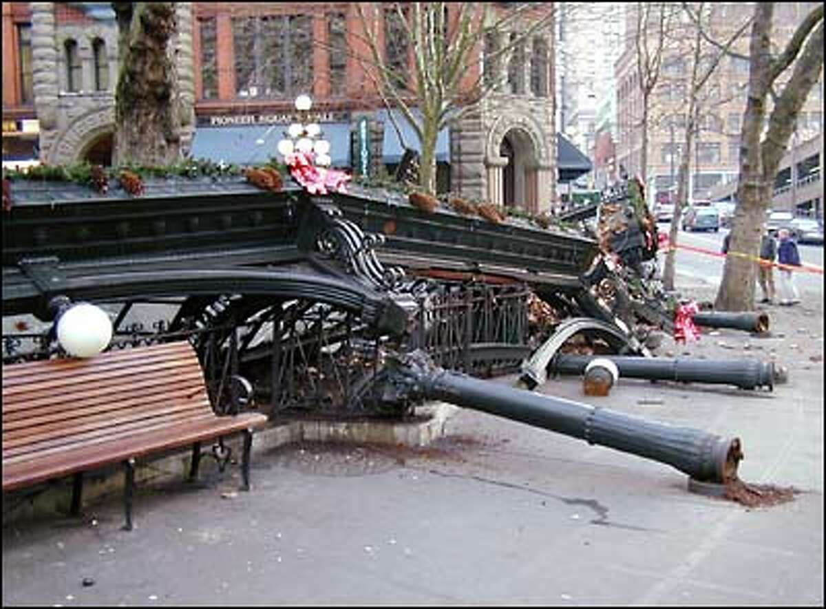 Still festooned with Christmas wreaths, the wreckage of Pioneer Square's historic pergola lies crumpled across the cobblestones.