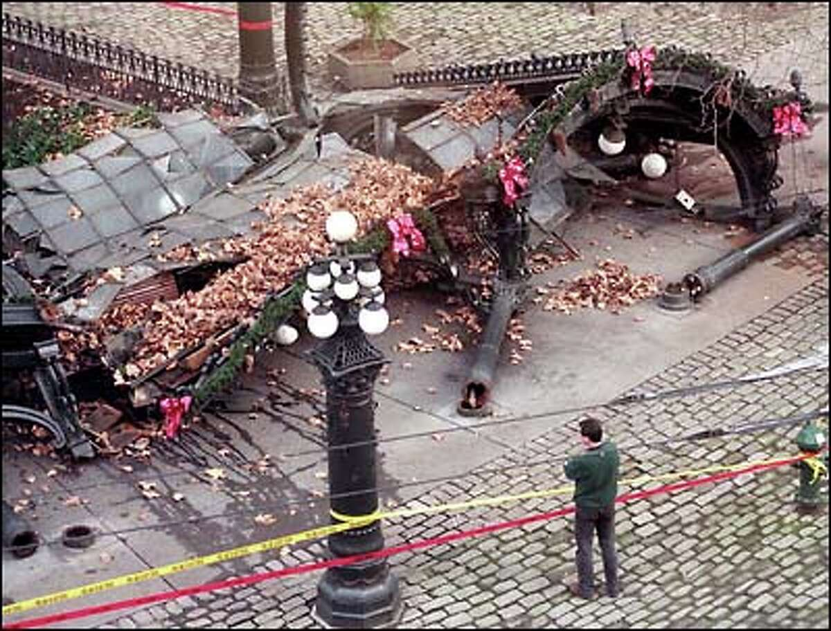 Still festooned with Christmas decorations, Pioneer Square's famous pergola lies shattered across the cobblestones after being hit by a commercial truck early Monday morning.