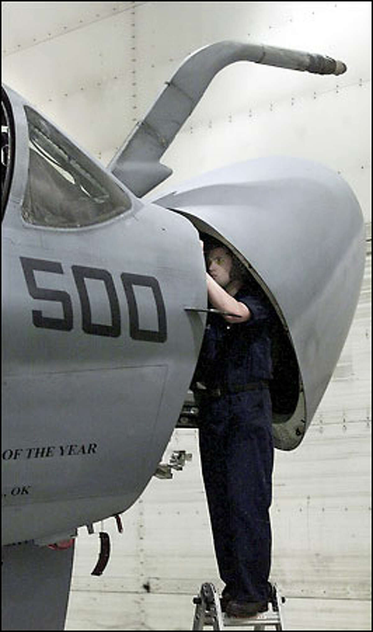 Avionics technician Alex Peake works on the nose of an EA6-B Prowler.