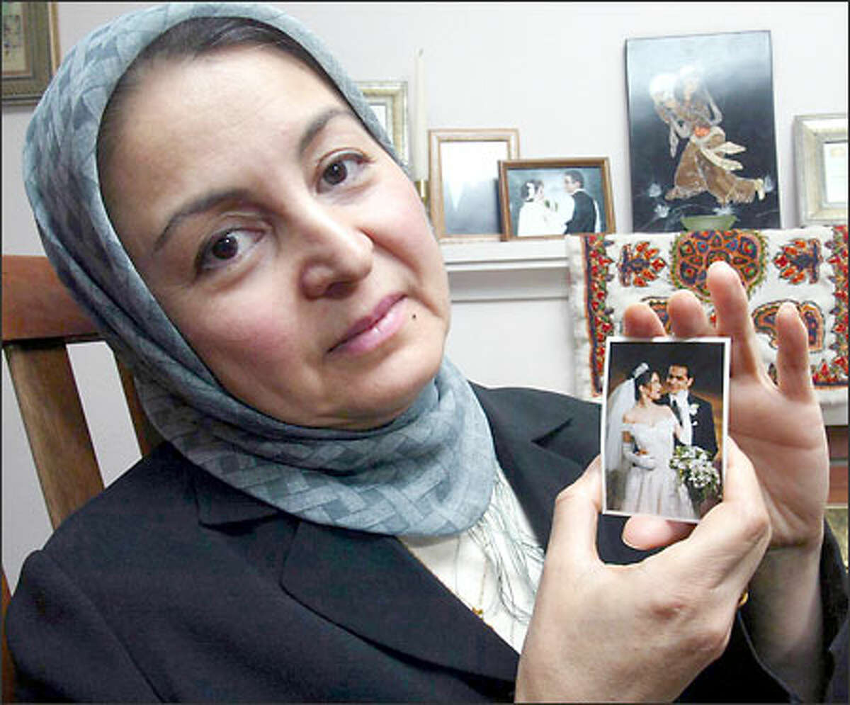 Fatima Bannazadeh holds a wedding photo of her friends Zoia Amiry and Mohsen Memarzadeh, who died in last month's quake in Bam, Iran.