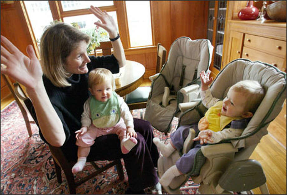"Jane Schmidt Campbell gets her daughter Esmé to sign ""all done"" while holding Esmé's twin, Madeleine, in their Mount Baker home on Tuesday. The girls are 11 months old. Photo: Dan DeLong, Seattle Post-Intelligencer / Seattle Post-Intelligencer"