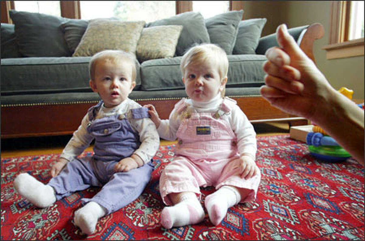 """Jane Schmidt Campbell tries to get her twin daughters Esmé, left, and Madeline to mimic her making the sign for """"milk."""""""