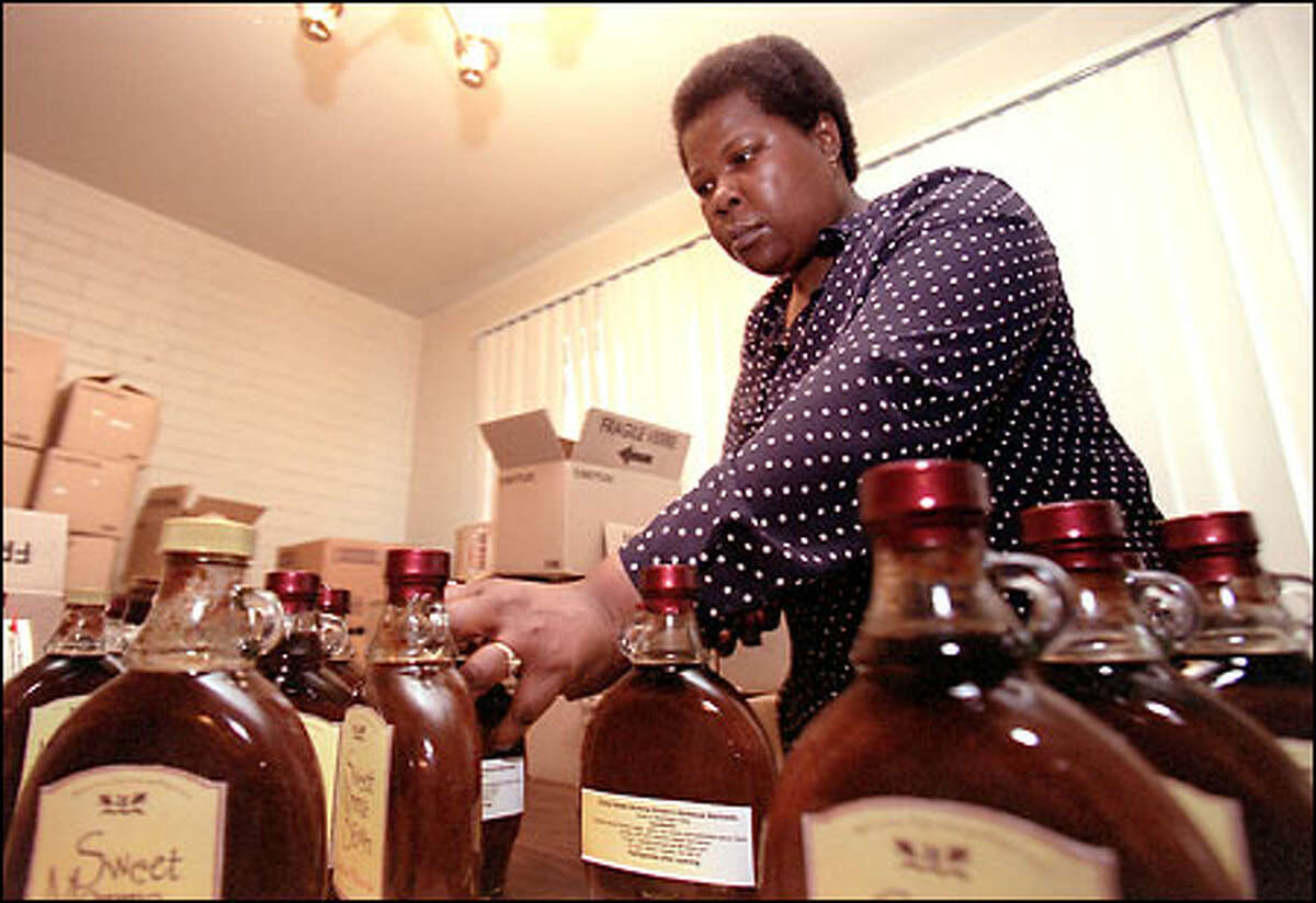 Juanita Mackey put the shrink wrap on a bottle of her Sweet Momma Brown's barbecue sauce, which is going to market with the help of Washington Cash.