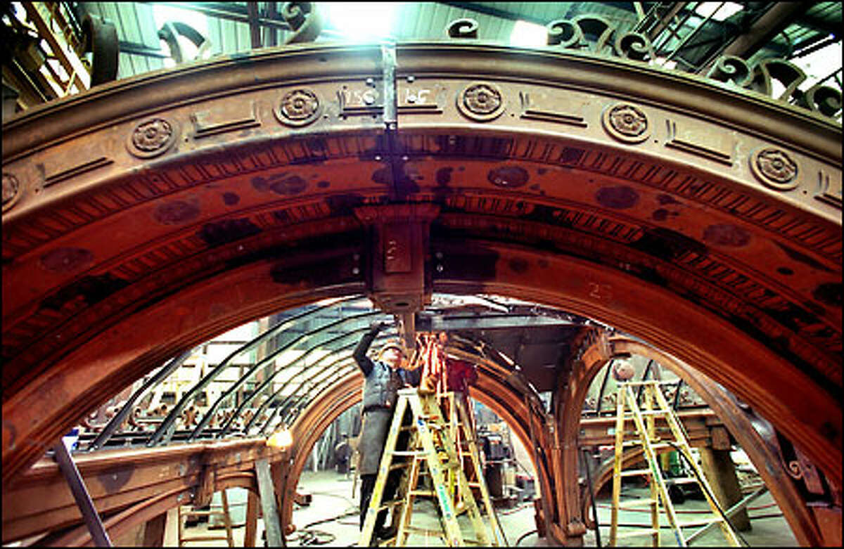A year after an 18-wheeler damaged the pergola in Pioneer Square, restoration of the venerable structure is at the halfway point at Seidelhuber Iron and Bronze Works. Foreman Tom Dike, center, holds a piece of Iron as Bob Fertado cuts from behind him. A six-man crew has been working five 10-hour days a week for the past three months on the project.