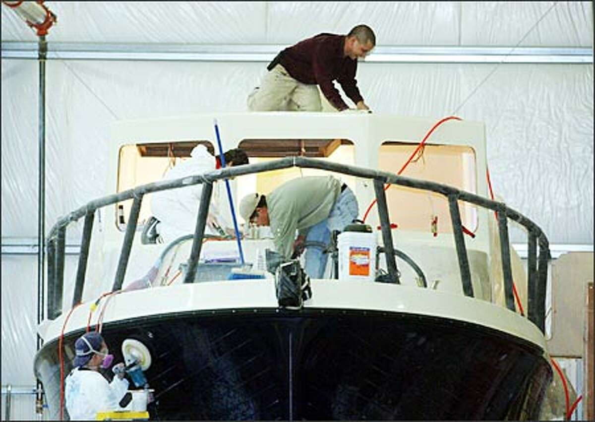Employees from Tomco Marine Group in La Conner work on American Tug 34, a 34-foot luxury craft that sells for $317,000. It will be on display at the Lake Union Boats Afloat Show (www.boatsafloatshow.com), which showcases more than 175 sail and motor yachts starting Friday at Chandler's Cove. Tickets cost $10.